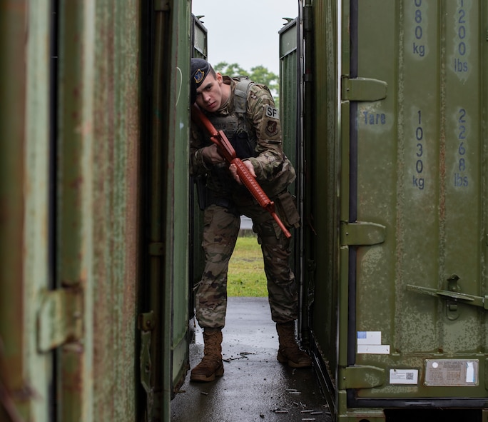 U.S. Air Force Airman Christopher Fuller, a 35th Security Forces Squadron entry controller, hides behind a shipping container during an agile combat employment exercise at Misawa Air Base, Japan, June 28, 2019. Fuller taught 35th Logistic Readiness Squadron how to move, shoot and communicate and applied their newly learned skills to realistic training scenarios, such as clearing buildings and shooting techniques during ACE. (U.S. Air Force photo by Staff Sgt. Brittany A. Chase)