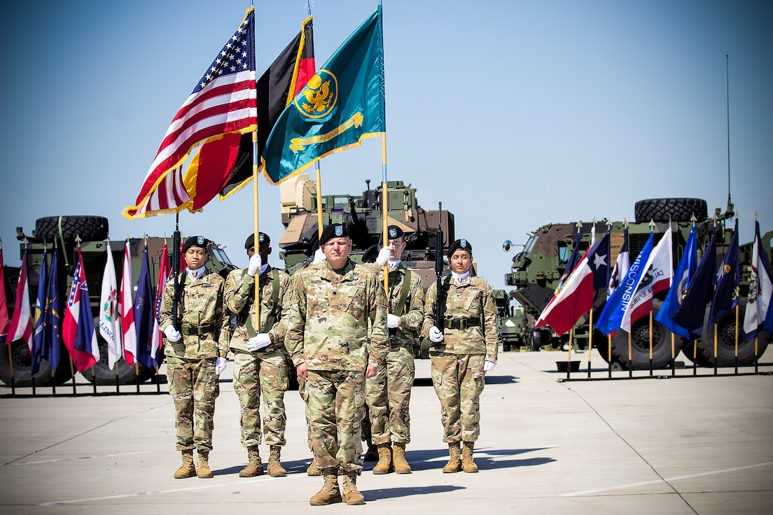 Lt. Col. Jason Knapp, incoming commander, Army Field Support Battalion- Mannheim, signs on as commander, in front of the battalion's color guard, during a change of command ceremony on Coleman Worksite in Mannheim, Germany, July 2