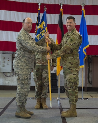 U.S. Air Force Col. Anthony Retka, 52nd Operational Group commander, left, gives  the ceremonial guidon to U.S. Air Force Lt. Col. Matthew Hoyt, incoming 52nd Operations Support Squadron commander, right, during the 52nd OSS change of command ceremony at Spangdahlem Air Base, Germany, July 03, 2019. (U.S. Air Force photo by Airman 1st Class Branden Rae)