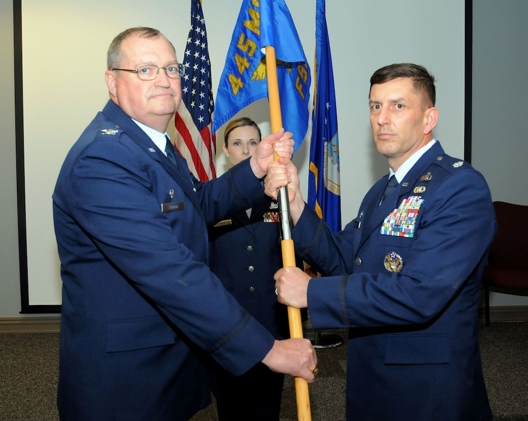 Col. Bryan Runion, 445th Mission Support Group commander, passes the guidon to Lt. Col. Darby Bess, incoming 445th Force Support Squadron commander, during an assumption of command ceremony June 2, 2019.