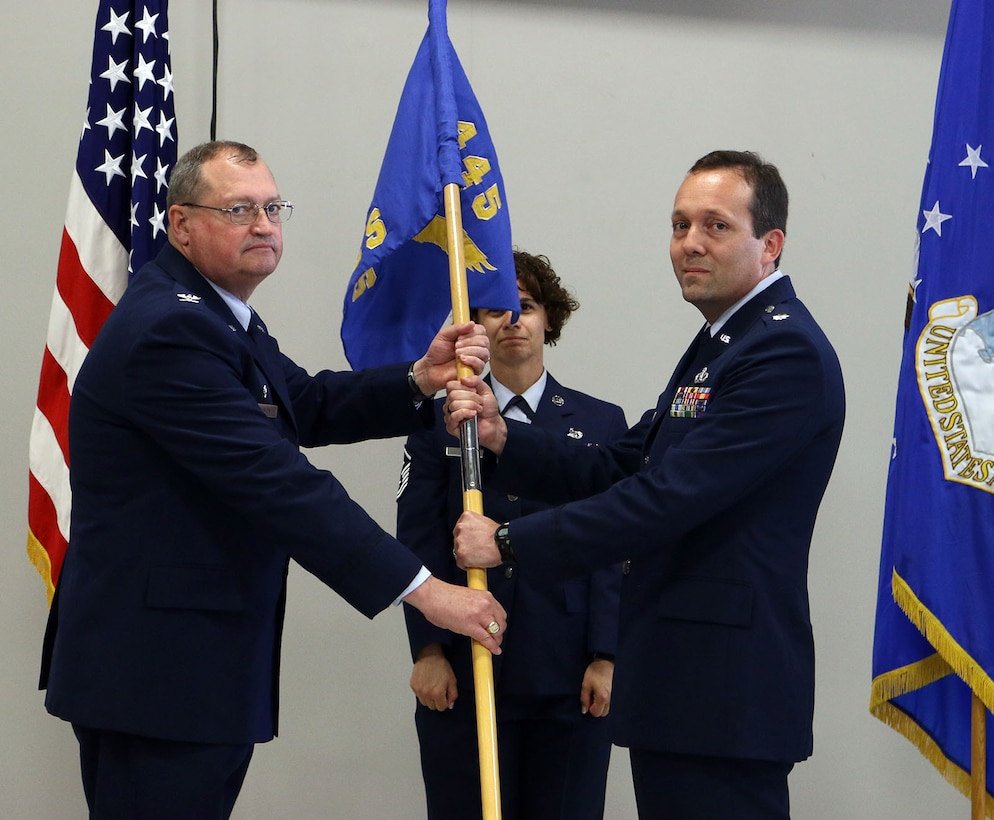 Col. Bryan Runion, 445th Mission Support Group commander, passes the guidon to Lt. Col. Jason Bordas, incoming 445th Civil Engineer Squadron commander, during a change of command ceremony June 1, 2019.