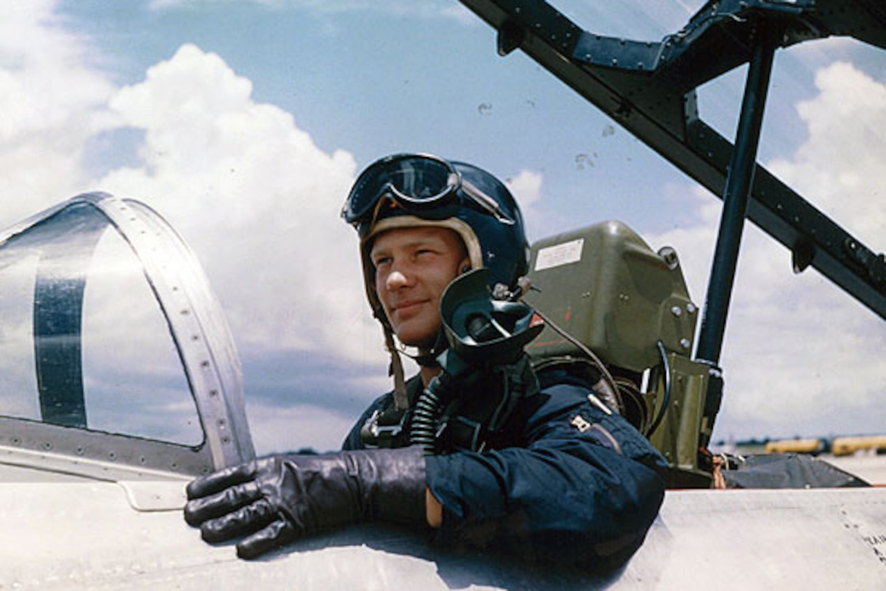 A man sits in an airplane cockpit smiling.