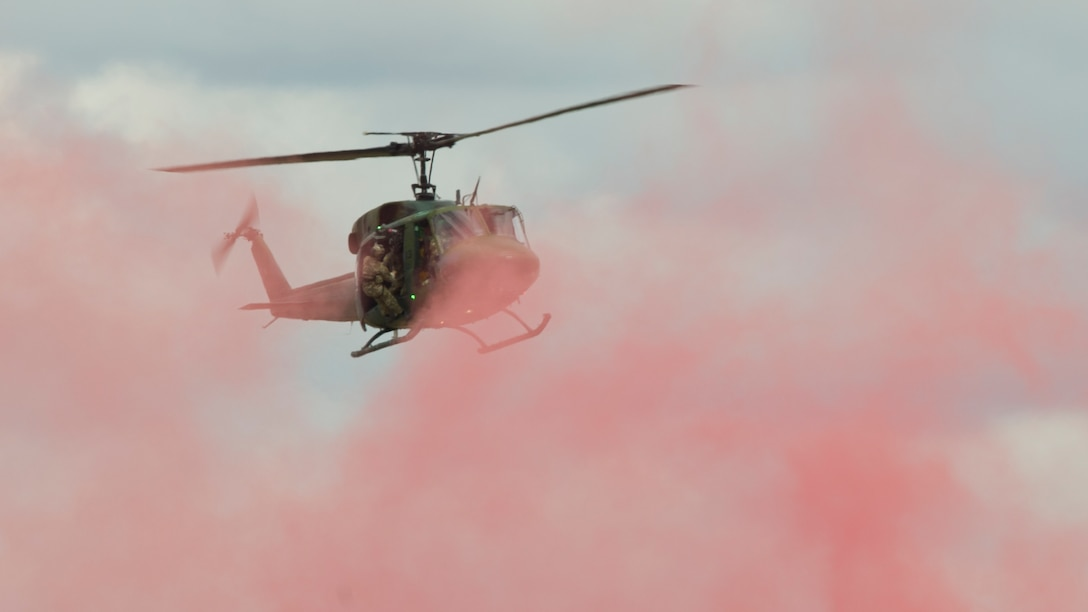 A UH-1 Iroquois helicopter from the 36th Rescue Squadron hovers over a marker-flare to perform a rescue demonstration at the 2019 Skyfest Open House and Air Show at Fairchild Air Force Base, Washington, June 22, 2019. Fairchild opened its gates to the public for a free one-day event to showcase Pacific Northwest airpower and U.S. Air Force capabilities. The airshow included the F-22 Demonstration Team, U.S. Army Golden Knights and 11 other aerial acts. (U.S. Air Force photo by Senior Airman Ryan Lackey)