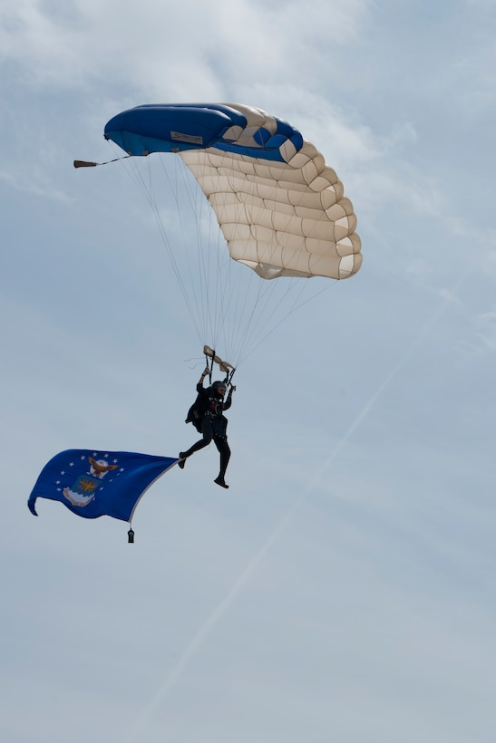 A U.S. Air Force Academy Wings of Blue parajumper glides in the flight line center stage while trailing the U.S. Air Force flag during the 2019 Skyfest Open House and Air Show at Fairchild Air Force Base, Washington, June 22, 2019. Skyfest 2019 offered a unique view of Team Fairchild's role in enabling Rapid Global Mobility for the U.S. Air Force. The show featured more than 13 aerial acts and 16 static display aircraft, as well as other attractions and displays. (U.S. Air Force photo by Senior Airman Ryan Lackey)