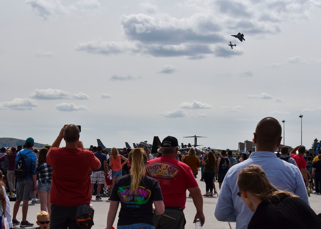 People at the 2019 Skyfest Open House and Airshow  watch a F-22 Raptor and a P-51 Mustang, on the flight line of Fairchild Air Force Base, Washington, June 22, 2019. Fairchild opened its gates to the public for a free one-day event to showcase Pacific Northwest airpower and U.S. Air Force capabilities. The airshow included the F-22 Demonstration Team, U.S. Army Golden Knights and 11 other aerial acts. (U.S. Air Force photo by Airman Kiaundra Miller)