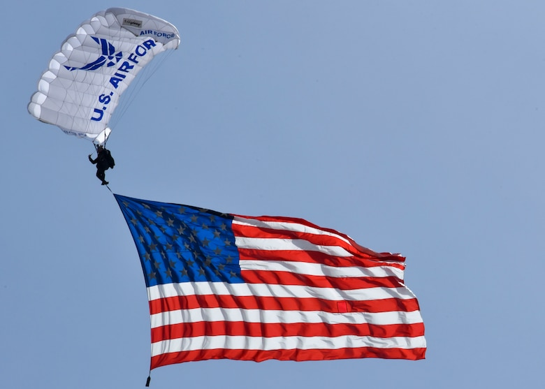U.S. Air Force Cadet Sara Hill, Air Force Academy Wings of Blue team member, jumps from a C-130 Hercules while carrying the American flag during the 2019 Skyfest Open House and Airshow  on Fairchild Air Force Base, Washington, June 22, 2019. Skyfest 2019 offered a unique view of Team Fairchild's role in enabling Rapid Global Mobility for the U.S. Air Force. The show featured more than 13 aerial acts and 16 static display aircraft, as well as other attractions and displays. (U.S. Air Force photo by Airman Kiaundra Miller)