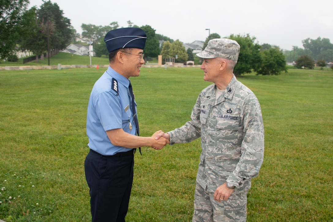 Col. Kyun Do Ki, left, Republic of Korea Air Force Weather Wing commander, and Col. Brian Pukall, right, 557th Weather Wing commander, shake hands in front of the 557th WW's headquarters building at Offutt Air Force Base, Nebraska, June 20, 2019. The visit included mission briefs, a tour of the wing headquarters and discussions of topics including data sharing and future cooperation. (U.S. Air Force photo by Paul Shirk)