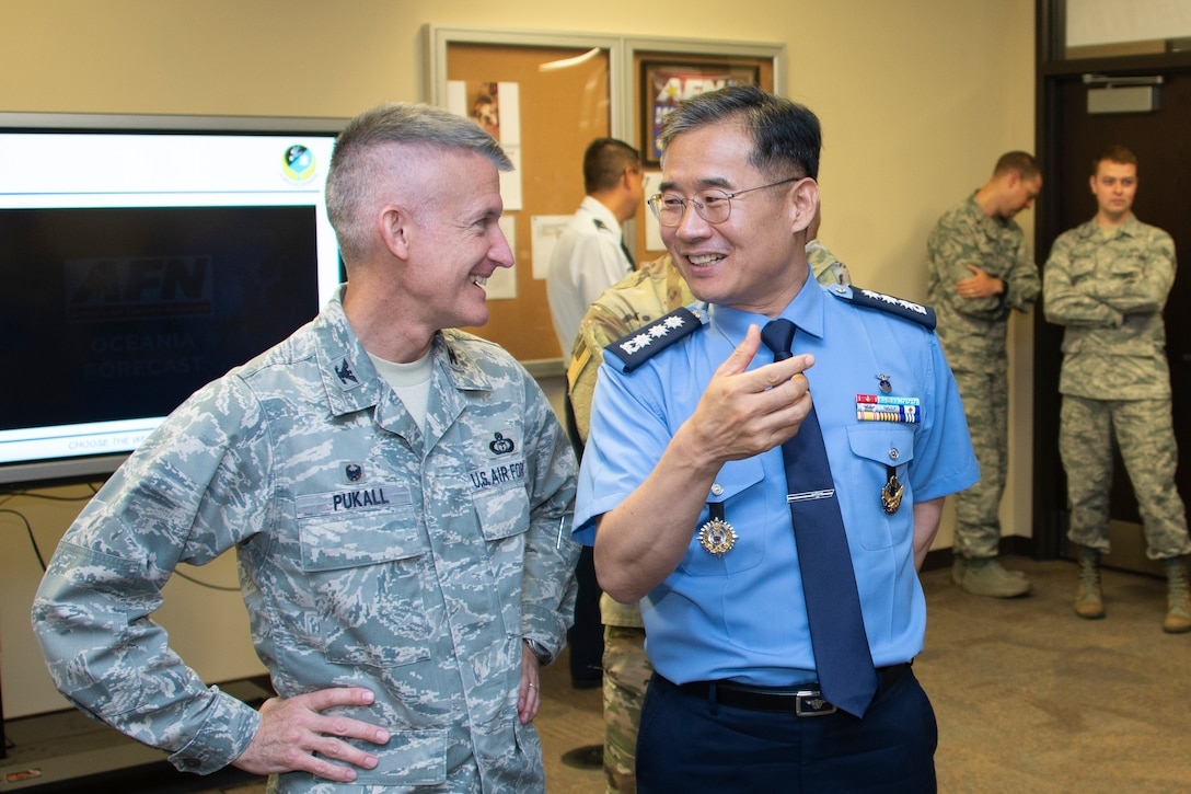 Col. Brian Pukall, left, 557th Weather Wing commander, and Col. Kyun Do Ki, right, Republic of Korea Air Force Weather Wing commander, talk during a demonstration at the American Forces Network Weather Center at the 557th WW headquarters building, Offutt Air Force Base, Nebraska, June 20, 2019. The AFN Weather Center records daily weather forecasts for the AFN audience as well as Stars and Stripes readers around the world. (U.S. Air Force photo by Paul Shirk)