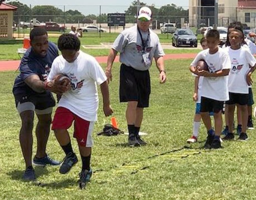 Houston Texans running back Lamar Miller (left) hosted a football camp for about 150 Joint Base San Antonio-Randolph Air Force Base youth from the first through eighth grades July 1-2. Miller, who has been with the Texans for three seasons, led the football camp to help military children to learn the game of football and live healthier lifestyles.