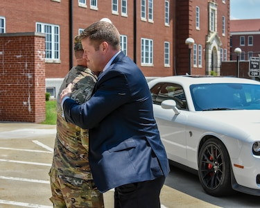 US soldier hugs a man in a suit.