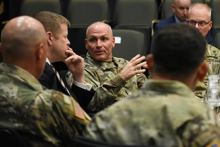 US soldiers talk with a man in a suit.