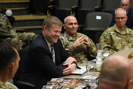 US soldiers with a man in a suit smiling.