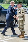 Army soldier shakes hands with a man in a suit.