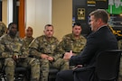 US Army soldiers speak with a man in a suit.