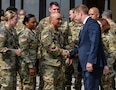 US Army soldiers shake hands with a man in a suit.