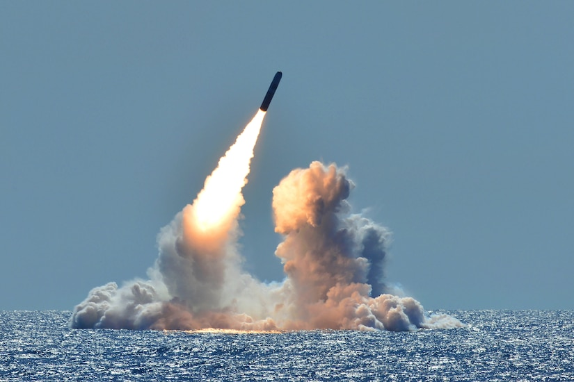 A missile launches from the ocean amid clouds of smoke.