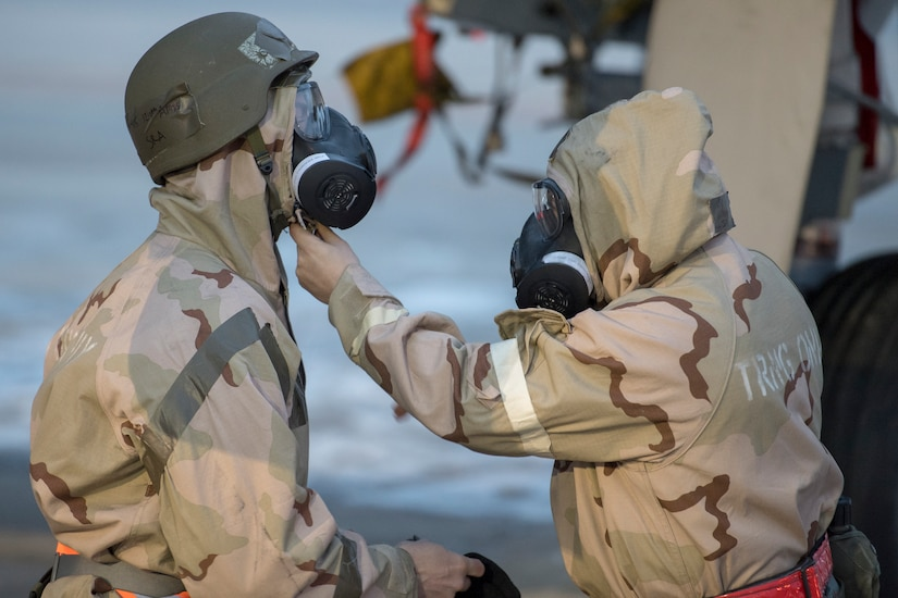 Two service members in chemical warfare gear check each other's gas masks.