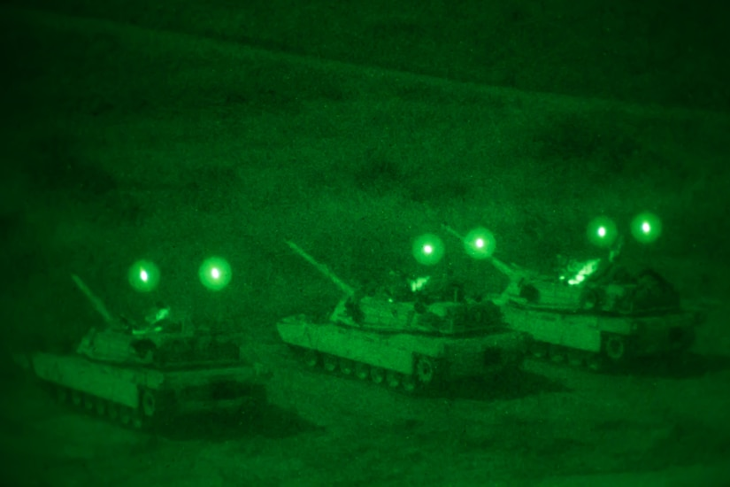 Three tanks are lined up side by side at night time.