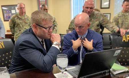 man in a suit looks at a laptop with another man in a suit.
