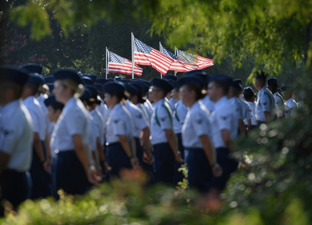 U.S. Flags blow in the wind as Airmen from the 81st Training Group stand in formation during the 81st TRG change of command ceremony on the Levitow Training Support Facility drill pad at Keesler Air Force Base, Mississippi, July 1, 2019. U.S. Air Force Col. Chance Geray, incoming 81st TRG commander, assumed command from Col. Leo Lawson, Jr., outgoing 81st TRG commander. (U.S. Air Force photo by Kemberly Groue)