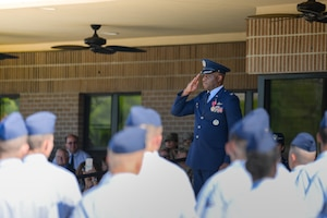 U.S Air Force Col. Leo Lawson Jr., outgoing 81st Training Group commander, salutes Airmen as they march during the 81st TRG change of command ceremony on the Levitow Training Support Facility drill pad at Keesler Air Force Base, Mississippi, July 1, 2019. The ceremony is a symbol of command being exchanged from one commander to the next by the handing-off of a ceremonial guidon.  Lawson's next assignment is to the United States Transportation Command.  (U.S Air Force photo by Airman 1st Class Spencer Tobler)