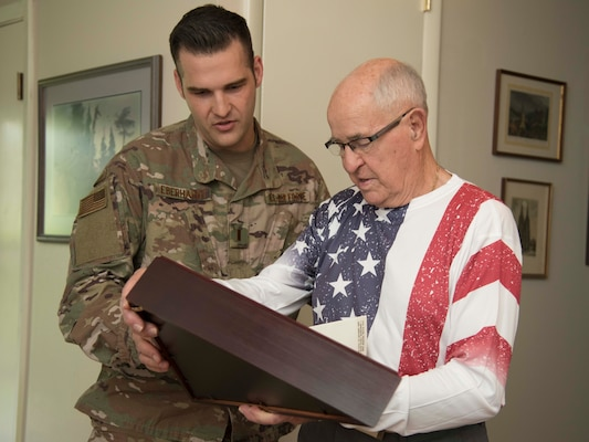 Robert C. Bueker, a local retiree and former World War II prisoner of war looks at flag that was given to him, with First Lt. Christian Eberhardt, 502d Air Base Wing Public Affairs Officer at his home July 3, 2019. Bueker celebrated his 95th birthday a day early with the help of Joint Base San Antonio presenting him with a personalized letter from Col. Mark Robinson, commander of the 12th Flying Training Wing, and a flag that has been flown onboard an F-16 during 2017 support operations in Afghanistan. (U.S. Air Force photo by: Airman 1st Class Shelby Pruitt)