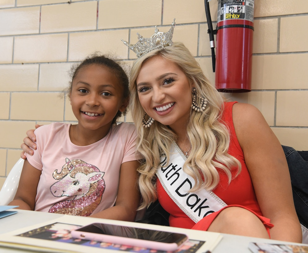 Amber Hulse, Miss South Dakota takes a photo with Angelisse Griffin during at the Summer Splash event at Ellsworth Air Force Base, S.D., July 1, 2019. Hulse came out to meet children on base, sign autographs and take photos with participants. (U.S. Air Force photo by Senior Airman Thomas Karol)
