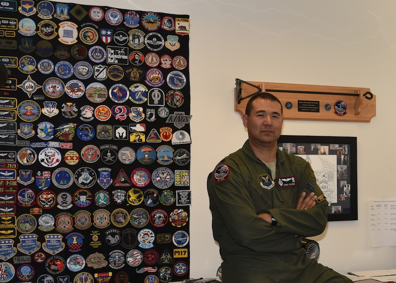 Lieutenant Colonel Christopher Picinni, 90th Operation Support Squadron director of operations, sits next to his patch wall with pride, July 2, 2019, on F.E. Warren Air Force Base Wyo. Picinni has collected a vast array of patches from various exercises, assigned units, and promotions. (U.S. Air Force photo by Senior Airman Braydon Williams)