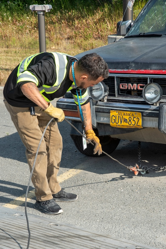 Edison Minyatty, an assistant tow truck operator with JT Towing LLC, adjusts chains attached to a vehicle July 1, 2019, on Joint Base Elmendorf-Richardson, Alaska. Abandoned and illegally parked vehicles on Joint Base Elmendorf-Richardson, Alaska, are towed because they present safety hazards.