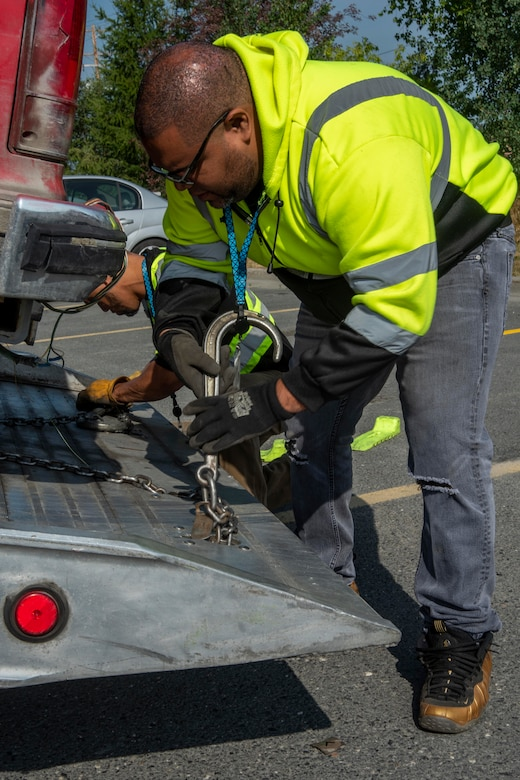 Edison Minyatty, an assistant tow truck operator with JT Towing LLC, and Jonathan Mejia, owner of JT Towing, secure a vehicle to a tow truck with chains July 1, 2019, on Joint Base Elmendorf-Richardson, Alaska. Abandoned and illegally parked vehicles on Joint Base Elmendorf-Richardson, Alaska, are towed because they present safety hazards.