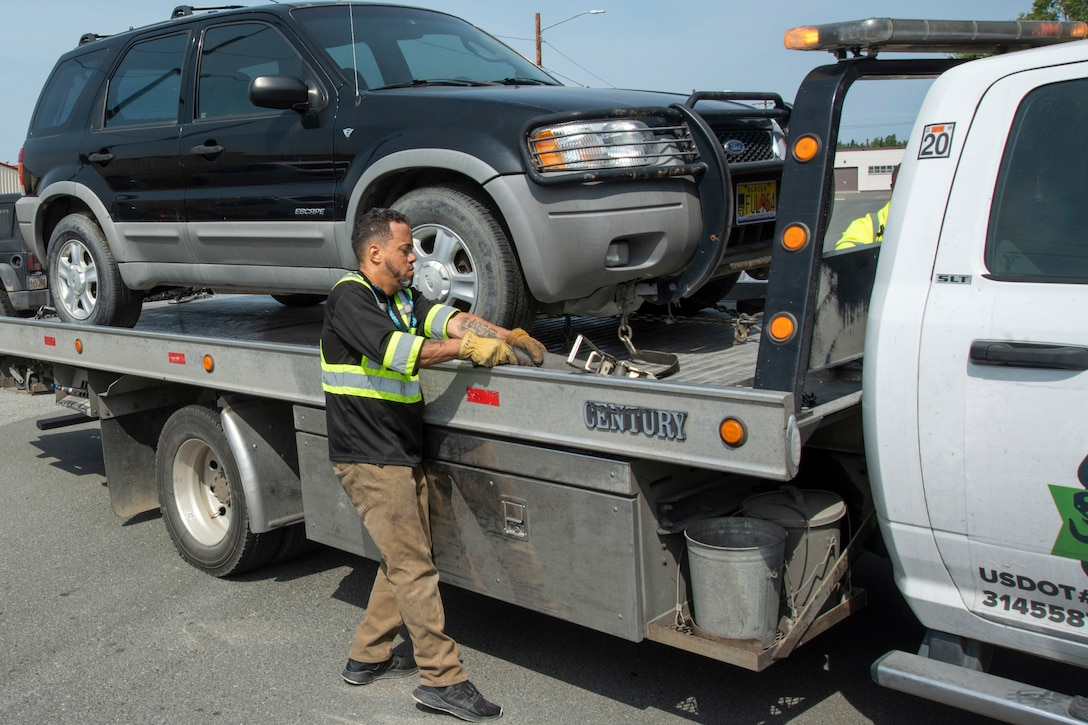Edison Minyatty, an assistant tow truck operator with JT Towing LLC, tightens a strap to secure a vehicle to a tow truck July 1, 2019, on Joint Base Elmendorf-Richardson, Alaska. Abandoned and illegally parked vehicles on Joint Base Elmendorf-Richardson, Alaska, are towed because they present safety hazards.