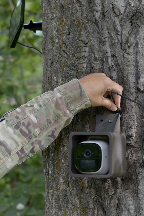 U.S. Air Force Master Sgt. Justin McDonald, a 673d Security Forces Squadron noncommissioned officer in charge of future operations, connects a camera during a high-definition, two-way camera unveiling near a wildlife access point on Joint Base Elmendorf-Richardson, Alaska, July 2, 2019. The unveiling of the cameras was a result of an MD5 workshop focused on the commander's priority of improving gate security and efficiency. The cameras were installed to prevent unauthorized entry onto the installation. (U.S. Air Force photo by Airman 1st Class Emily Farnsworth)