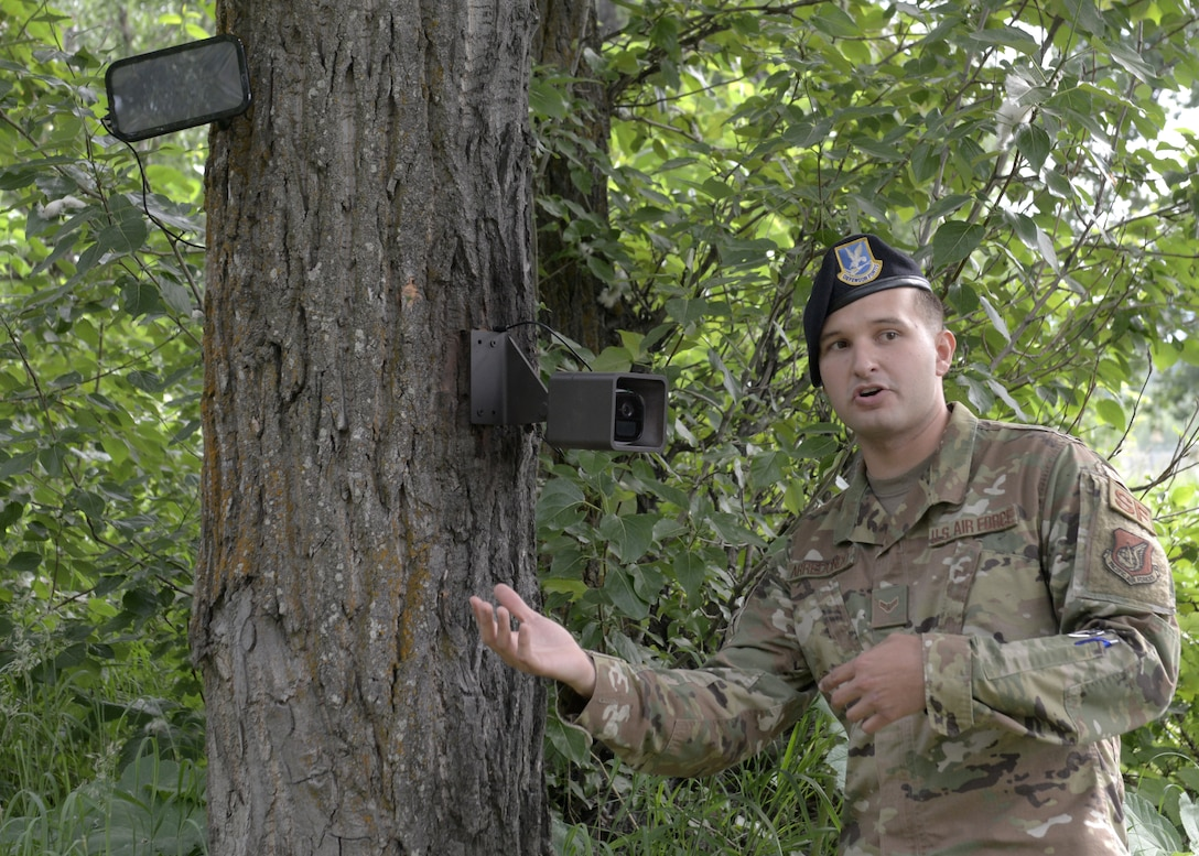U.S. Air Force Airman 1st Class Stefan Arredondo, a 673d Air Base Wing Arctic Spark Council marketing and networking assistant, discuss a camera's impact on Joint Base Elmendorf-Richardson's mission during a high-definition, two-way camera unveiling near a wildlife access point on Joint Base Elmendorf-Richardson, Alaska, July, 2, 2019. The unveiling of the cameras was a result of an MD5 workshop focused on the commander's priority of improving gate security and efficiency. The cameras were installed to prevent unauthorized entry onto the installation. (U.S. Air Force photo by Airman 1st Class Emily Farnsworth)