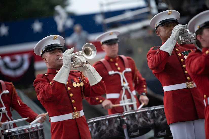 A marine in a red uniform plays a trumpet.