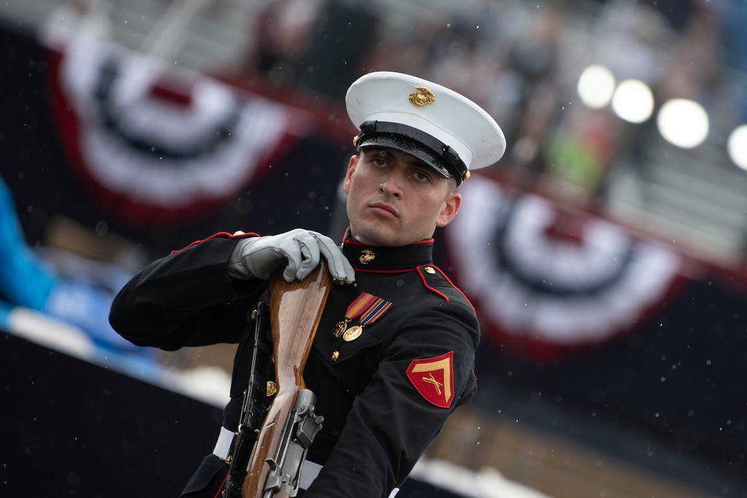 A marine in uniform holds a gun during a ceremony.