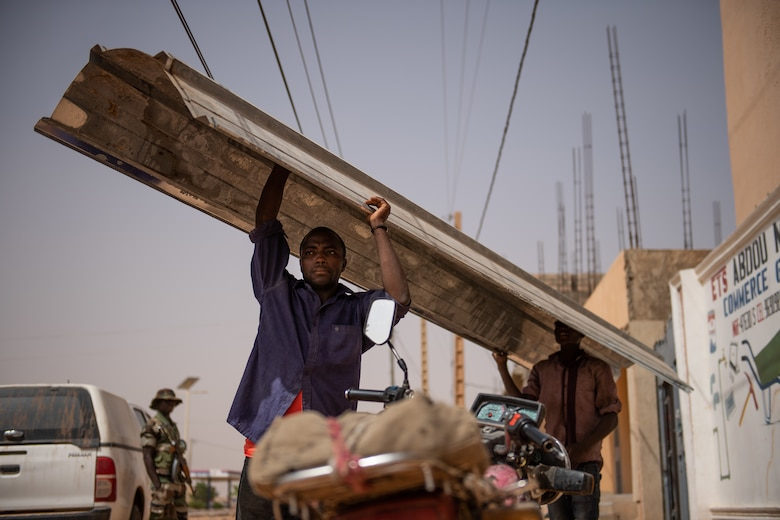Nigerien employees from a local hardware store carry a sheet of tin roofing to a truck in Agadez, Niger, June 27, 2019. The 724th Expeditionary Air Base Squadron civil engineer flight installed the roofing on two classrooms in local villages. (U.S. Air Force photo by Staff Sgt. Devin Boyer)