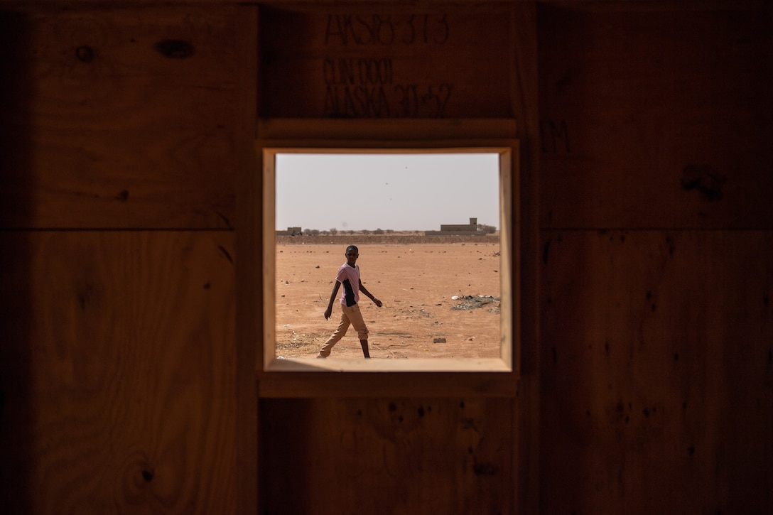 A Nigerien boy observes the recent construction on a classroom built by 724th Expeditionary Air Base Squadron civil engineer flight Airmen at a village in Agadez, Niger, June 27, 2019. The village's previous classrooms were made of wooden sticks with a thatched roof. (U.S. Air Force photo by Staff Sgt. Devin Boyer)