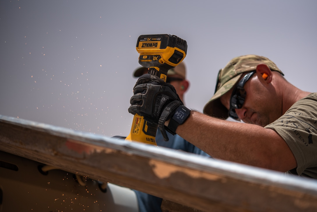U.S. Air Force Tech. Sgt. Kelly Warren, 724th Expeditionary Air Base Squadron civil engineer flight structural craftsman, cuts a sheet of tin roofing at a village in Agadez, Niger, June 27, 2019. The civil engineer Airmen installed the tin roof on a classroom they built for the local Nigeriens. (U.S. Air Force photo by Staff Sgt. Devin Boyer)