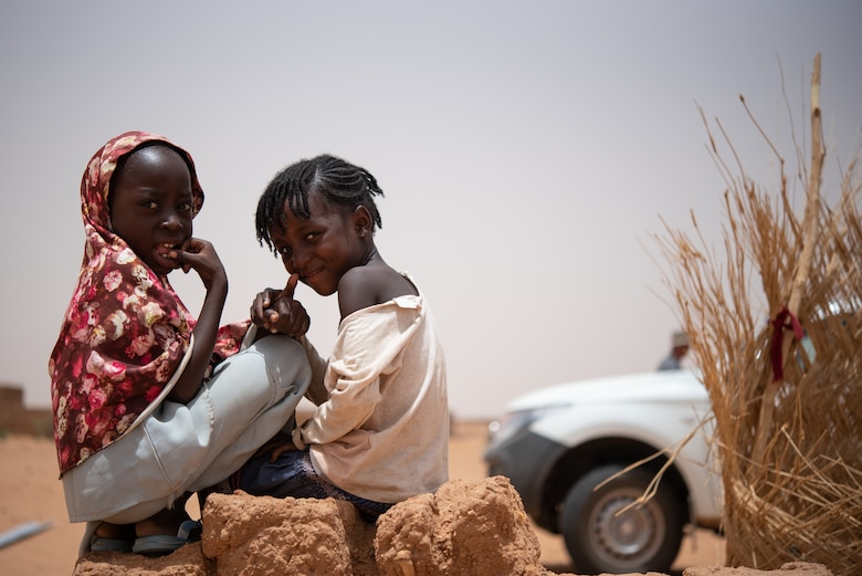 Two Nigerien girls sit on a pile of mudbrick at a village in Agadez, Niger, June 27, 2019. Most structures in Agadez are made from mudbrick which can be created by mixing mud, sand, and water with a binding material such as rice husks or straw. (U.S. Air Force photo by Staff Sgt. Devin Boyer)
