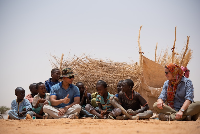 U.S. Air Force Maj. Hoang Nguyen, 435th Air Expeditionary Wing chaplain, and U.S. Army Staff Sgt. Cana Garrison, Civil Affairs Team 204, interact with Nigerien children at a village in Agadez, Niger, June 27, 2019. The civil affairs team helps connect the local community with the military community, which strengthens their partnership. (U.S. Air Force photo by Staff Sgt. Devin Boyer)