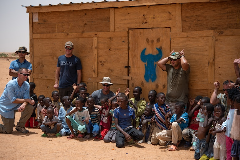U.S. Airmen and Soldiers from Air Base 201 pose for a photo in front of a classroom with Nigeriens at a village in Agadez, Niger, June 27, 2019. The 724th Expeditionary Air Base Squadron civil engineer flight built the classroom for the village. (U.S. Air Force photo by Staff Sgt. Devin Boyer)