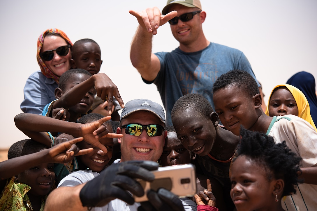 U.S. Air Force Staff Sgt. Jacob Johnson, 435th Air Expeditionary Wing chaplain assistant, takes a selfie with Nigerien children at a village in Agadez, Niger, June 27, 2019. Johnson assisted the 724th Expeditionary Air Base Squadron civil engineer flight with constructing a classroom for the village. (U.S. Air Force photo by Staff Sgt. Devin Boyer)