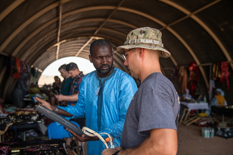 A vendor sells souvenirs to a U.S. service member assigned to Nigerien Air Base 201 during a bazaar at the base in Agadez, Niger, June 30, 2019. The bazaar gives local Nigeriens a chance to sell their products so they can help their villages while strengthening the relationship with the military community.  (U.S. Air Force photo by Staff Sgt. Devin Boyer)