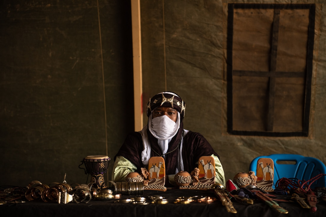 A vendor sits behind a table of hand-made souvenirs during a bazaar at Nigerien Air Base 201 in Agadez, Niger, June 30, 2019. The bazaar hosted 43 vendors selling bracelets, masks, blankets, bags, and various other souvenirs. (U.S. Air Force photo by Staff Sgt. Devin Boyer)