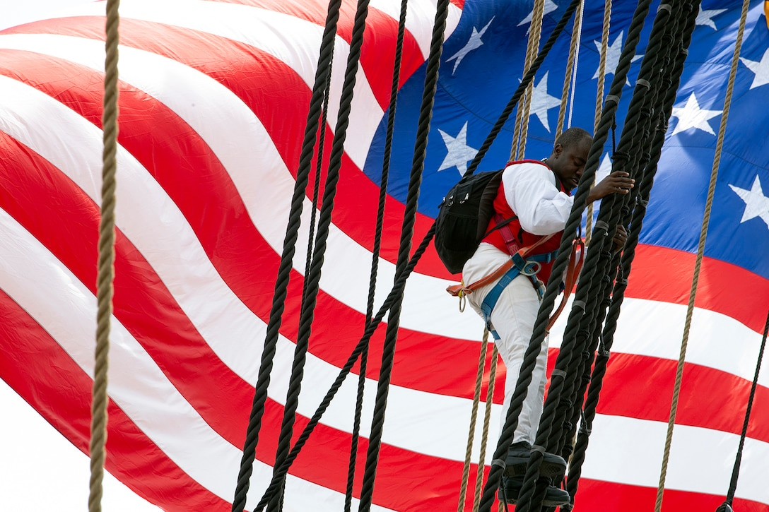 A sailor climbs down the rigging of the USS Constitution while a large American flag waves behind him.