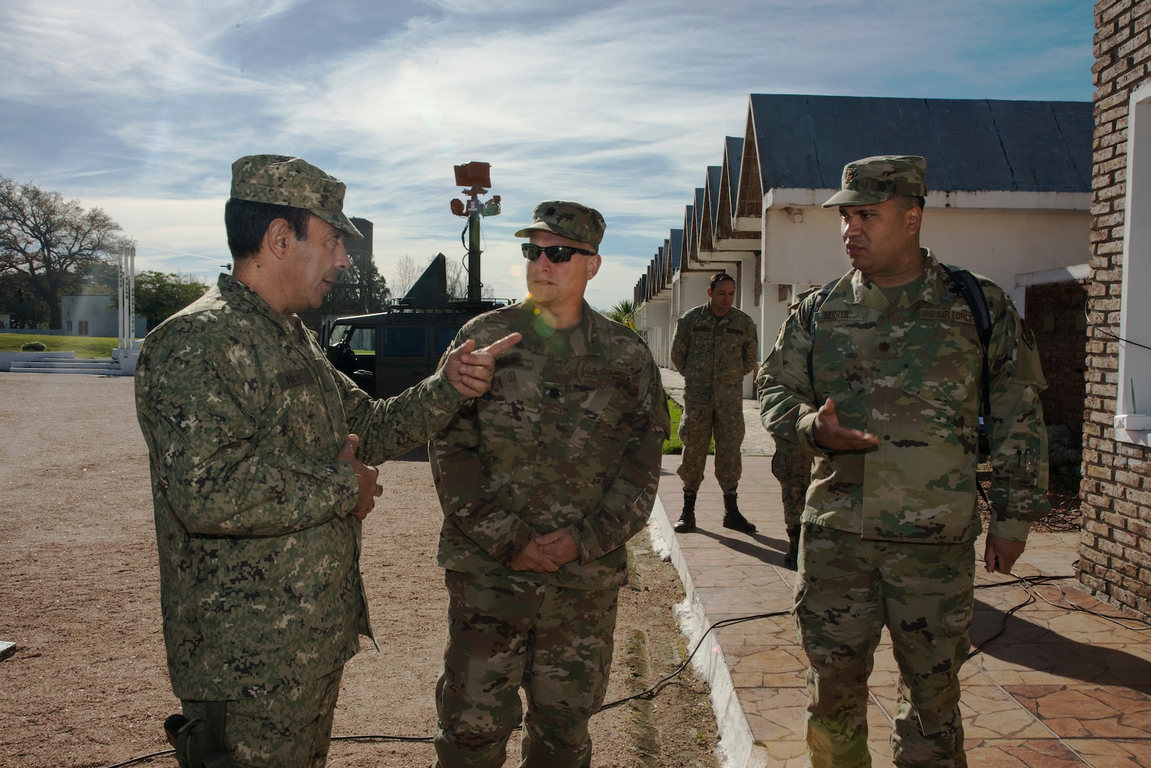 Uruguayan Army Colonel Dyver M. Neme, Communications Brigade One Commander, left, discusses the Uruguayan Army's communications capabilities with Lt. Col. Guy Marino, 103rd Air Control Squadron, center, and Maj. David Ferrer, Connecticut State Partnership Program Director in Montevideo, Uruguay, June 27, 2019.