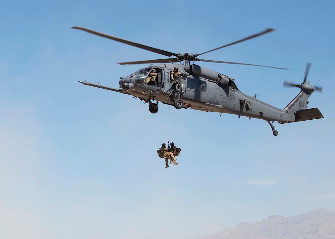The 66th Rescue Squadron rappel from an HH-60G Pave Hawk helicopter