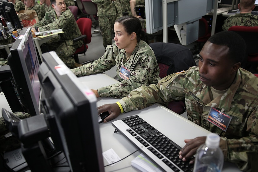 Two uniformed military personnel, one with the U.S. Navy, and one with the U.S. Army, operate computers.