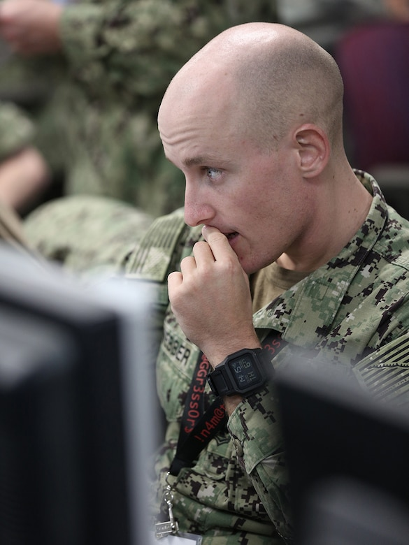 A lone uniformed service member reads a computer screen.  His fingers are pressed to his lips, and he appears concerned.
