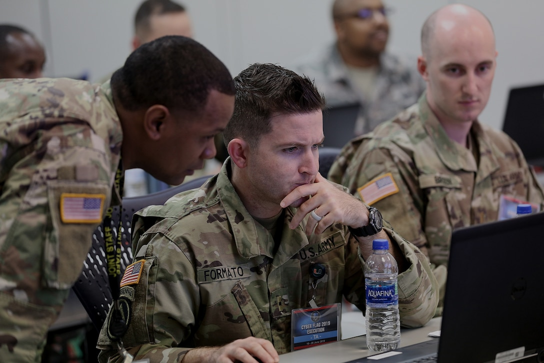 A U.S. service member sits at a desk operating a computer.  Another service members stands next to him.